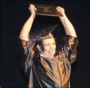 Tracy Wendell holds up her bachelor of science in nursing diploma. She was among about 375 receiving degrees Saturday.