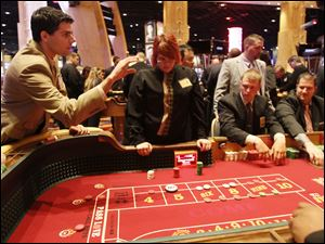 David Garewal of Cleveland rolls the dice as staff members practice at the Hollywood Casino Monday.
