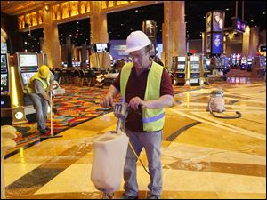 Workers clean and buff the floor at the Hollywood Casino.