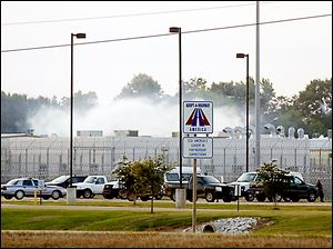 Smoke rises above the Adams County Correctional Center in Natchez, Miss., Sunday, during an inmate disturbance at the prison.