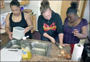 Instructor Teri Easter, center, helps Katrina Phillips, left, and Evelyn Wright during a cooking class offered by the Seagate Food Bank. Students must have a child under 4 and must commit to the full eight-week class.