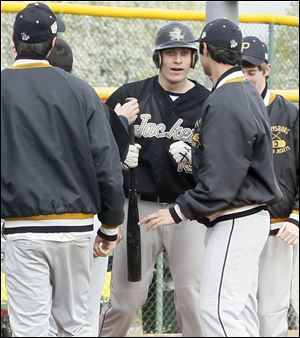 Perrysburg High School's designated hitter Hunter Smith, center, is congratulated by his teammates at home plate after hitting a home run.