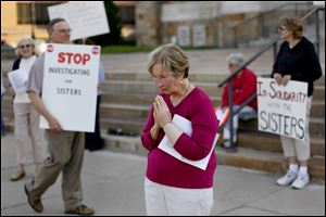 Pat Hanusz, of Corpus Christi University Church, prays in front of Rosary Cathedral on Tuesday in support of Catholic nuns.  Hanusz said,