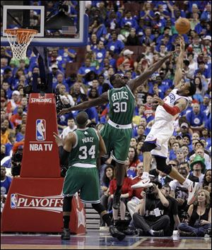 Philadelphia 76ers' Andre Iguodala, right, goes up for a shot as Boston Celtics' Brandon Bass, center, and Paul Pierce defend during the first half of Game 6.