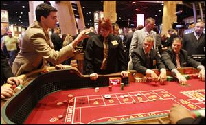 David Garewal of Cleveland rolls the dice as staff members practice at the Hollywood Casino in Toledo during a recent media tour of the facility.