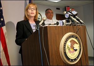 Carole Rendon, 1st Assistant U.S.Attorney, discusses the charges filed against 18 people stemming from raids last fall at a number of area IHOP restaurants, during a news conference at the U.S. Attorney's office in Toledo.  Deputy Toledo Police Chief George Taylor is at back right.  A majority of  the charges are for money laundering, harboring of illegal immigrants, and identity theft.