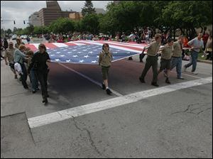 Marchers carry a large American flag down Jackson Street during the Memorial Day Parade in downtown Toledo last year.