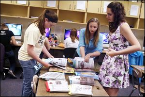Co-editors Megan Russ, left, Samantha Sieren, and Kelly Kilpatrick sort through extra issues of the student-run newspaper, The Somethin'. It was first published at Perrysburg High School in 1922.