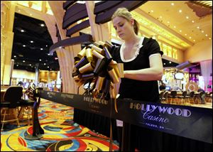Brianna Chipps of Toledo puts up the ribbon to be cut at Hollywood Casino Toledo's  grand opening ceremony.