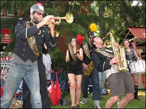 The Detroit Party Marching Band, including John Notarianni on trumpet, left, Elle Gotham, on cymbals, and Paul Mardirosian, on tenor, all of Detroit, play at last year's Old West End Festival.
