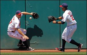 Cleveland Indians left fielder Shelley Duncan, left, and center fielder Michael Brantley try to corral an RBI double off the left center wall by Kansas City Royals' Alex Gordon in the fourth inning.