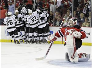 New Jersey Devils' goalie Martin Brodeur gets up from the ice after as the Los Angeles Kings celebrate their winning goal during the overtime period of Game 1.