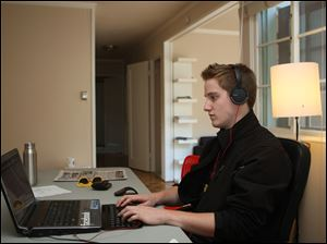 Eric Simons, 20, works in the living room of his rental cottage in Palo Alto, Calif., which he now can afford after earning the admiration of investors. He secretly camped out in AOL's offices for two months while starting his own company, ClassConnect.