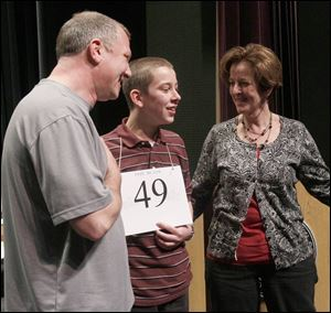 Spencer Hipsher, 13, a student at St. Wendelin in Fostoria, with his parents, Ron and Lynn Hipsher, is shown after winning the  Northwest Ohio Spelling Bee. He was eliminated from the national competition after three rounds on Wednesday.