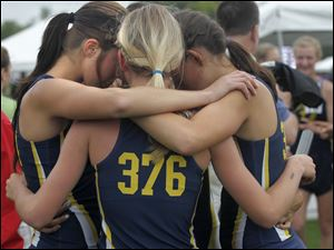 Archbold's 3200-relay team huddles after competing.