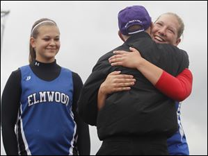 Elmwood's Kori Reiser watches as lead discus officer Dee Clay hugs girls discuss winner Alyssa Gary Liberty-Benton.
