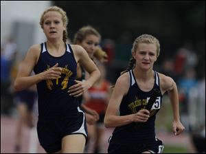 Toledo Christian's Delainey Phelps runs with the baton during the 3200-meter relay.