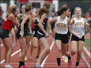 Northview's Mallory Small, second from left, takes the handoff from Abigail Masters during the 3200-meter relay.