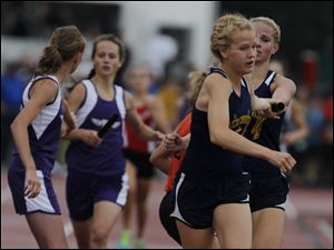 Toledo Christian's Krista Wood, front right, takes the baton from Darian Westmeyer during the 3200 relay.