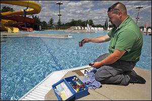 Mike Butcher, an inspector with the Toledo-Lucas County Health Department, checks the water quality at the Rolf Park Pool in Maumee, which opens for the season at noon Saturday.