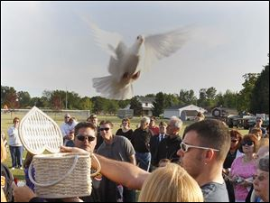 Pam Bowman and her son Shawn Bowman release a dove in memory of Bailey Bowman during a memorial service at the Millbury Veterans Memorial for the seven victims of the tornado two years ago in Millbury, Ohio. Pam is Bailey's mother and Shawn is Bailey's brother.