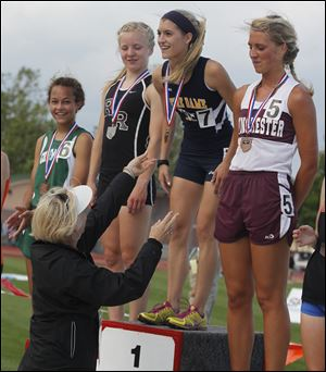 Notre Dame's Lexi Aughenbaugh receives her medal at the top of the awards podium after winning the 3200- meter race in the Division I state meet