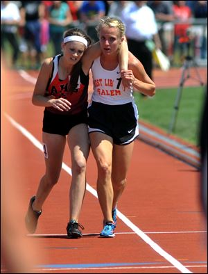 Meghan Vogel, right, helps Arden McMath to the finish line Saturday in Columbus in the 3,200-meter run.