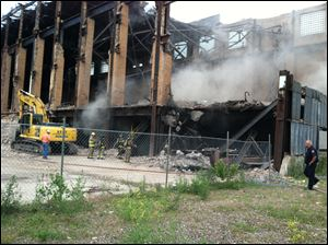 Debris at the Acme Power Plant in East Toledo was ignited today be workers dismantling the structure.