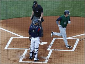 Hens catcher Rob Brantly watches Charlotte's Tyler Kuhn cross the plate after hitting a home run on the fourth pitch of the game.
