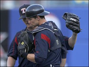 Starting Hens pitcher Thad Weber confers with catcher Rob Brantly during game against Charlotte.