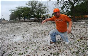 Steven Carpe sinks knee-deep in hail in the southwest parking lot of The Citadel mall Thursday after a hail and rain storm hit Colorado Springs, Colo., Wednesday night.