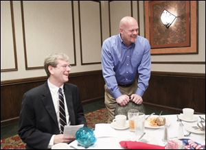 Jon Stainbrook, chairman of the Lucas County Republican party, seated, and Samuel 'Joe the Plumber' Wurzelbacher, who is running for Congress, chat with members of the Greater Toledo Republican Club at its annual banquet.