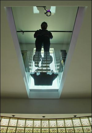 Interior designer Steve Levey stands on the structural glass floor he used in a west Akron residence.