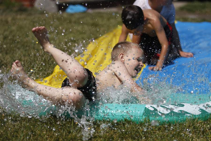 Zachary-Gross-8-cools-off-on-a-Slip-n-Slide