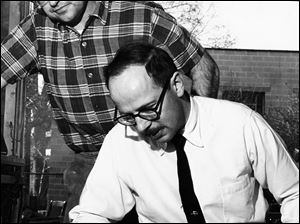 Harvey Littleton works with a piece of glass as Norman Schulman looks on during the 1962 Toledo workshop.