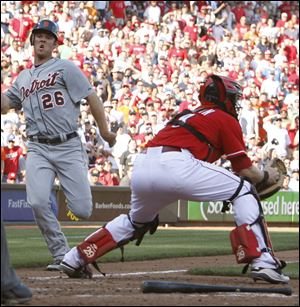 Detroit Tigers' Brennan Boesch (26) scores the go-ahead run at home plate ahead of Cincinnati Reds catcher Ryan Hanigan (29) after a single hit by Prince Fielder off Reds pitcher Sean Marshall in the eighth inning during a baseball game, Saturday.
