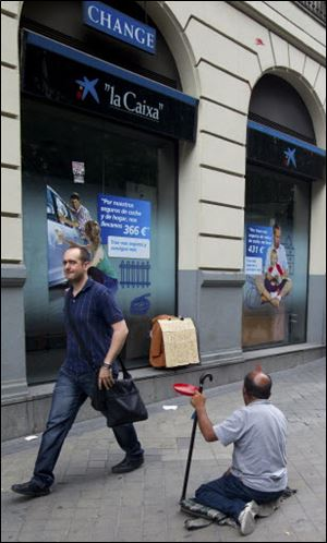 A man begs for money outside a bank in Madrid on Sunday. Spain's grinding financial misery will get worse this year despite the country's request for a European financial lifeline of up to $125 billion to save its banks, Prime Minister Mariano Rajoy said.
