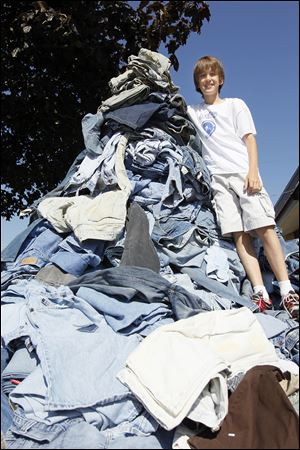Erek Hansen of Curtice, Ohio, stands on a pile of jeans. His goal is to send 5,000 pairs to Cotton: From Blue to Green, a group that collects denim to recycle into housing insulation.