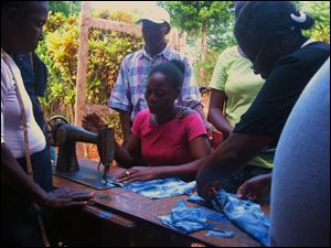 A Haitian woman learns how to operate one of the pedal-operated Singer sewing machines the Sisters of St. Francis of Sylvania have received to start a small business to help residents learn a trade to make money to support themselves.