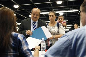 Jose Canales talks to a recruiter as he is accompanied by his wife, Magdel, and daughter Alexamarie at a job fair expo in Anaheim, Calif. More Americans sought unemployment aid last week.
