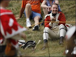 American revolution re-enactor Jeff Berndt of Waterford, Mi., enjoys a sword fight by the Combatants Keep during the Muster on the Maumee.