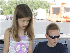 Anna Birdsell, 10, of Toledo, left, is fingerprinted by Tyler Wepler, of Holland, as part of the DNA Lifeprint Child Safety kit. Her biometric fingerprints are put on a disk for her to put with the rest of the kit.