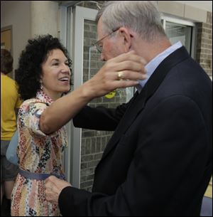 The Rev. Jim Bacik greets Martha Wheeler at Corpus Christi Parish. He has served at the parish since 1982.