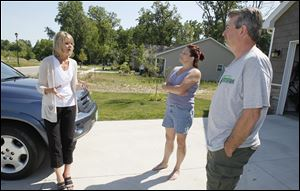Karen Hensley, left, talks with Ruth and John Insco outside their home in the GrayStone Woods subdivision in Toledo. Ms. Hensley's husband, Ron Hensley, is co-owner of the subdivision developer.