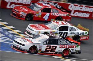 Brad Keselowski (22), Johanna Long (70), and Danny Efland (4) compete in the Nationwide race at Michigan International Speedway.