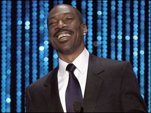 Eddie Murphy proudly shows off his gap between his front teeth.