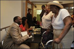Kwame Kilpatrick laughs with Audrey Johnson, second from right, and her mother, Mantle Smith, both of Toledo, as he signs an autograph in his book 'Surrendered … The Rise, Fall and Revelation of Kwame Kilpatrick' at the Worship Center.