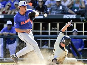 Kent State's Jimmy Rider scores on a wild pitch from Florida's Jonathon Crawford, left, in the fourth inning.