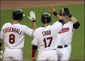Cleveland's Asdrubal Cabrera, right, is congratulated by Lonnie Chisenhall and Shin-Soo Choo after hitting a three-run home run off Cincinnati Reds pitcher Bronson Arroyo in the fourth inning Wednesday night in Cleveland. The Indians won 8-1 to complete a three-game sweep.
