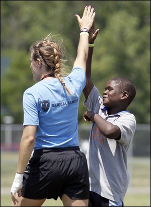 Mykul Hoskins, 10, and team leader Meghan Brown high-five during a soccer game. The local program began June 11 with 125 youths ages 10 to 16. In recent years NYSP at the University of Toledo has been recognized for its programs, lunches, and overall organization by various groups.